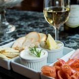 Traditional hungarian smoked ham, salami, cheese selection and bread with white wine - Wine Tasting